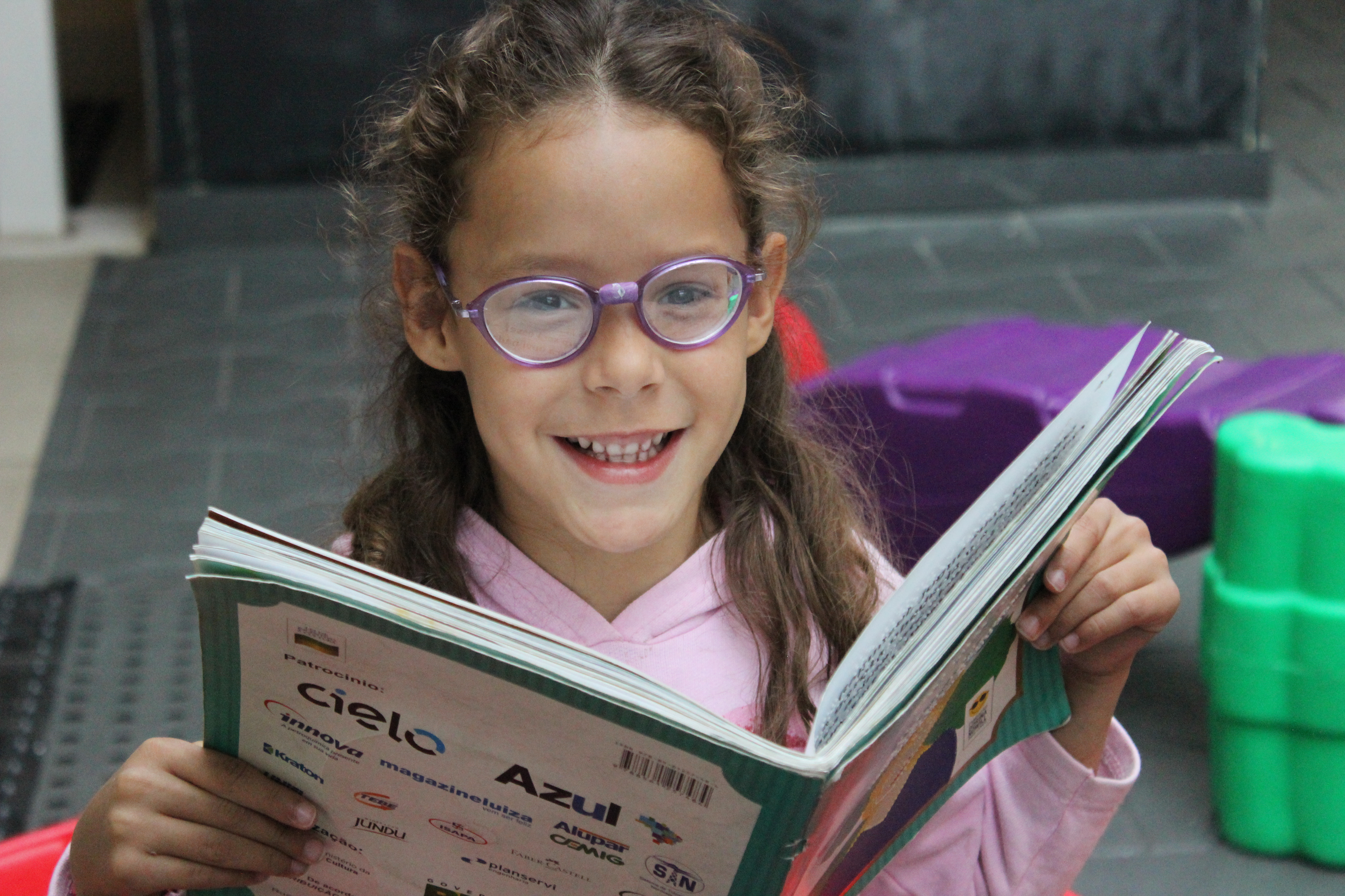 Foto de Ana Júlia, criança atendida pela Fundação. Ela está no parquinho da Fundação, segurando um livro aberto em sua frente e sorri. Ela veste blusa rosa e óculos de hastes na cor roxa.