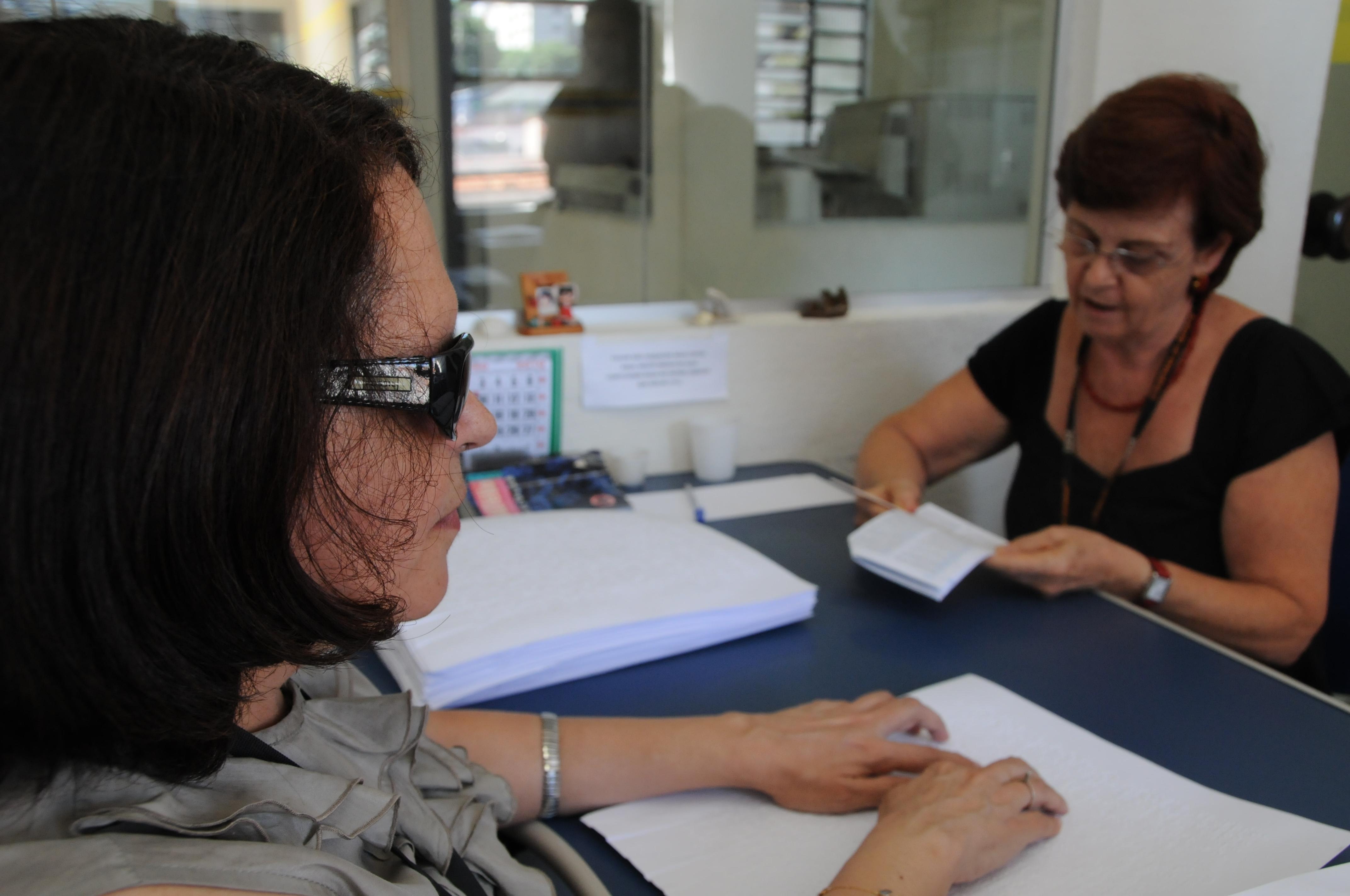 Foto de uma cena de revisão. Regina Oliveira está em primeiro plano, de perfil, lendo uma página braille, sobre uma mesa a sua frente. Do outro lado da mesa, de frente para Regina, está uma mulher segurando nas mãos páginas com texto escrito.