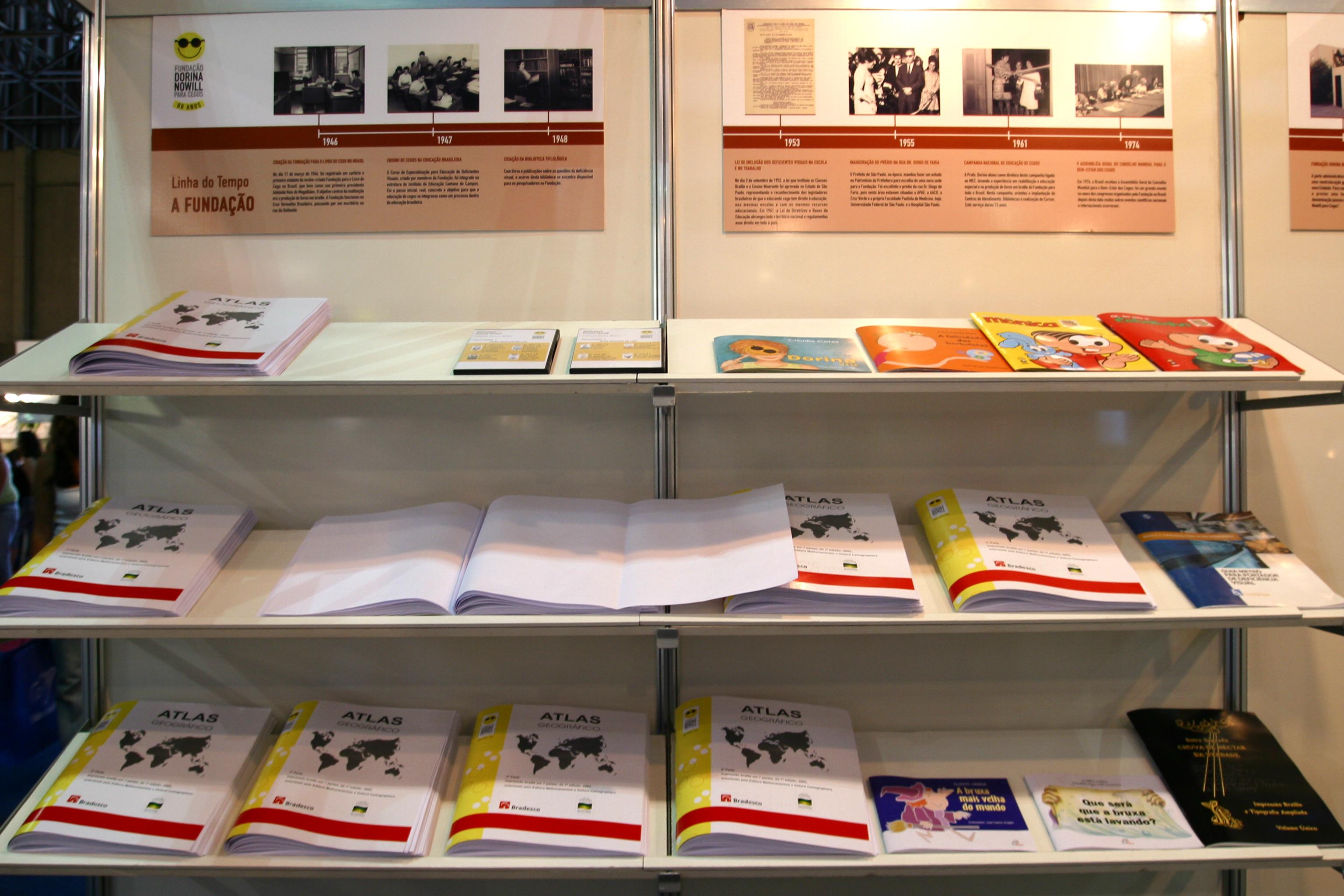 Imagem de uma estante com várias prateleiras e sobre elas vários livros em braille, desde infantis até didáticos. Acima da estante há uma linha do tempo da Fundação Dorina fixada na parede, composta por textos e imagens.