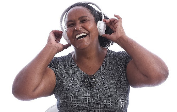 Descrição da imagem: foto de Fernanda, uma mulher negra retratada da cintura pra cima, com fones de ouvido brancos na cabeça. Ela toca o equipamento com as duas mãos e exibe um largo sorriso de olhos fechados.
