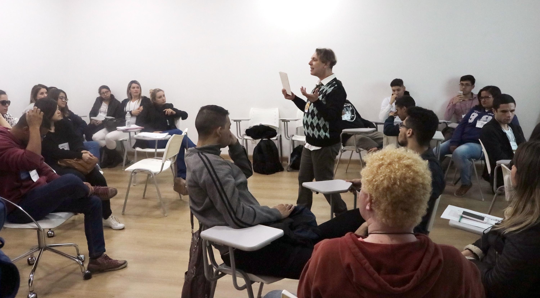 Descrição da imagem: foto de homem de pé, rodeado por dezenas de pessoas sentadas em cadeiras universitárias em uma sala de paredes brancas.