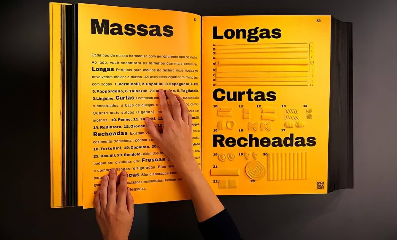 """Descrição da imagem: foto de duas mãos tocando um livro aberto. O livro tem páginas amarelas e texto na cor preta com letras grandes. Em tamanho maior há o título """"Massas: longas, curtas, recheadas"""". Na página à direita há também diferentes formatos de massas em relevo."""