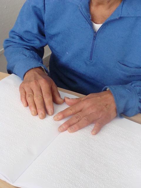 Descrição de imagem: fotografia colorida de mãos tateando um livro em braille.