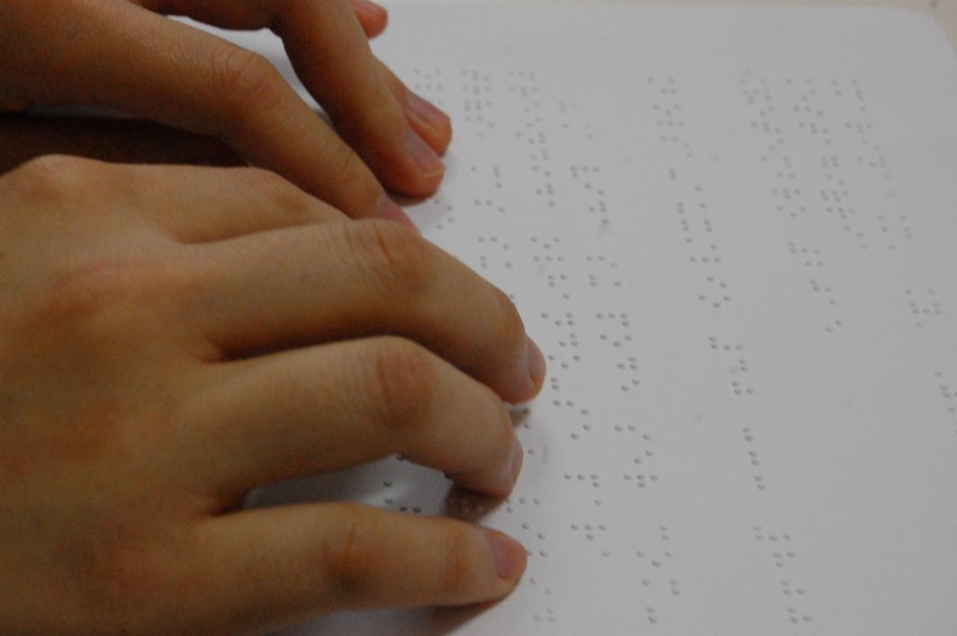 Descrição de imagem: Mãos leem um material em braille. Fim da descrição.