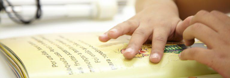 Foto das mãos de uma criança lendo um livro braile.