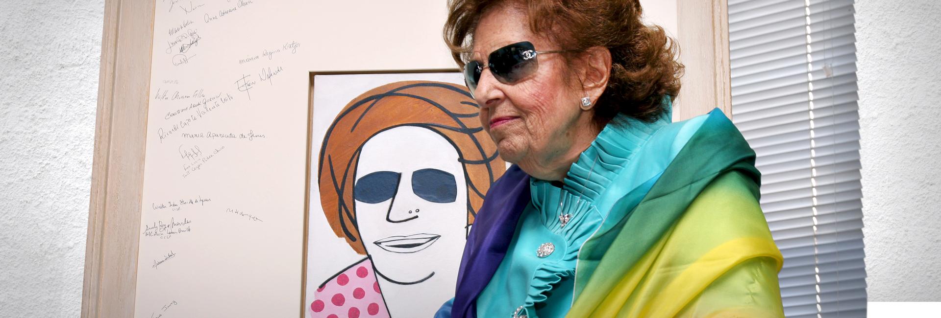Foto de Dorina Nowill em frente a um quadro feito em sua homenagem. No quadro há uma caricatura sua e em volta a assinatura de entes queridos.