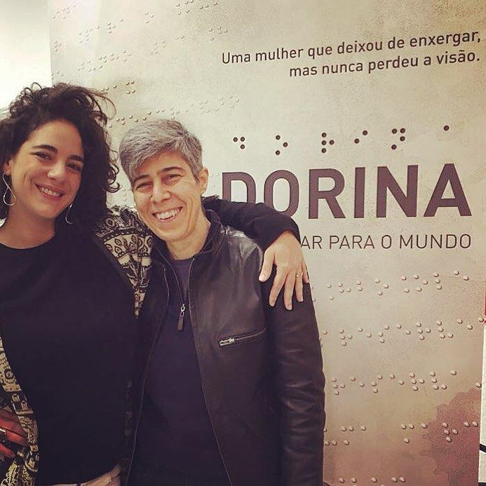 Descrição da imagem: Fotografia colorida de Marta Nowill e Lina Chamie em frente ao painel de divulgação do filme.