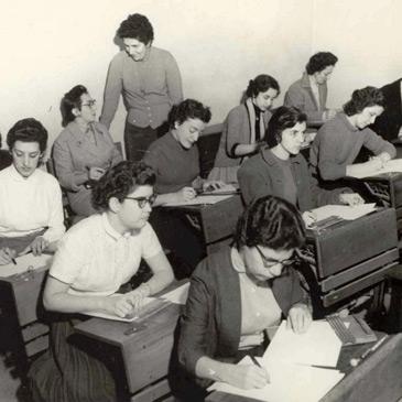 Foto antiga em preto e branco, Dorina Nowill está em pé em meio a uma sala de aula composta por mulheres.