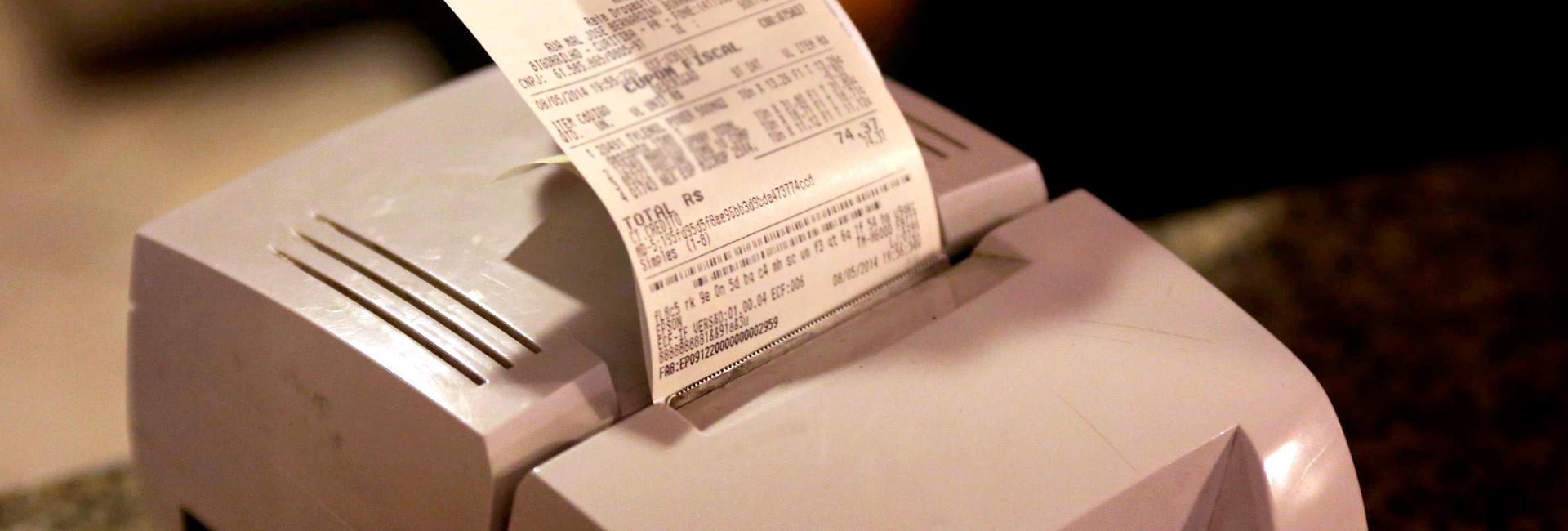 Foto de um cupom fiscal saindo da impressora.