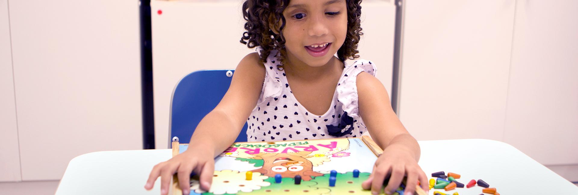 Foto de uma criança com deficiência visual atendida pela fundação Dorina. Ela está sorrindo com um brinquedo educativo numa mesa.
