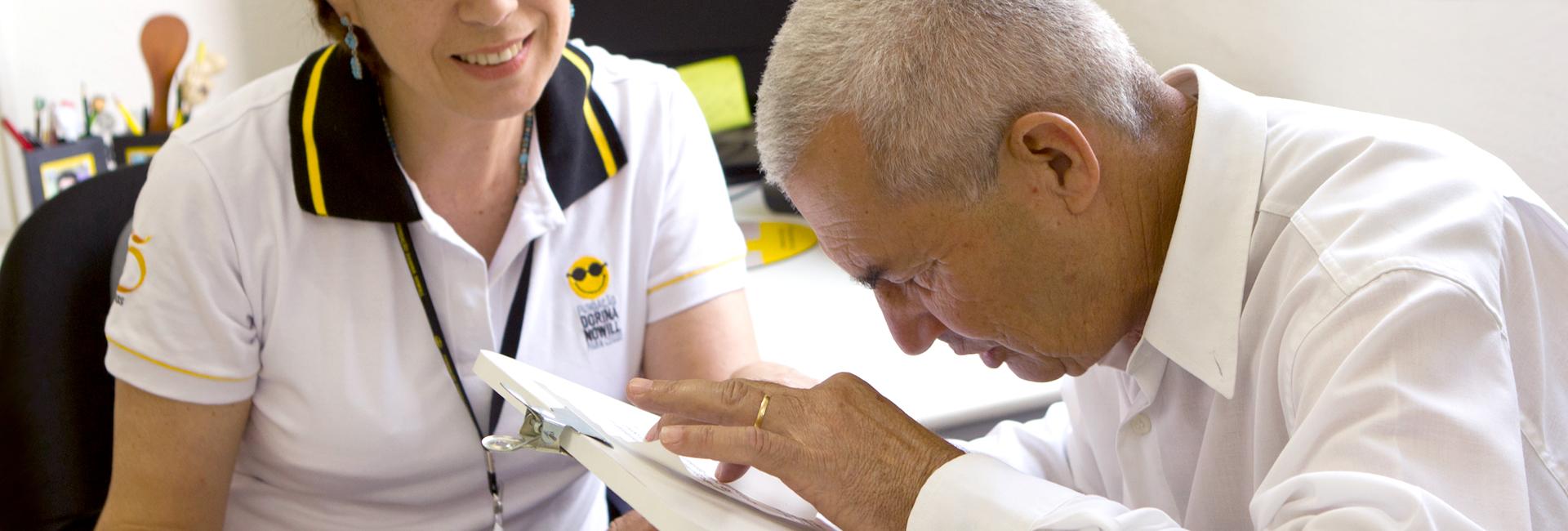 Foto de um senhor com deficiência visual, lendo e sendo auxiliado por uma profissional da fundação Dorina.