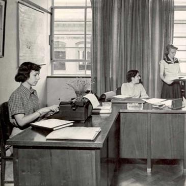 Foto em preto e Branco de um escritório nos primórdios da fundação Dorina, nele há três mulheres trabalhando.