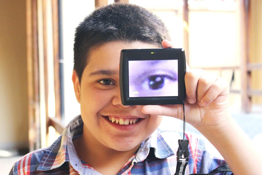 Descrição da imagem: foto de menino sorridente segurando uma lupa eletrônica na frente do olho esquerdo. A tela do aparelho exibe o olho do menino ampliado.