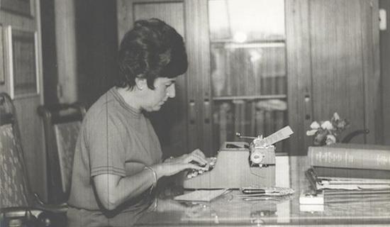 Foto em preto e branco de Dorina Nowill sentada a uma mesa utilizando uma máquina de escrever.