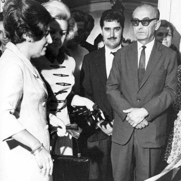 Foto em preto e branco de Dorina Nowill com um grupo de aproximadamente 10 pessoas em trajes sociais. Alguns olham em direção à câmera.