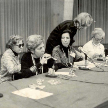 Foto de Dorina Nowill falando ao microfone. Ao seu lado estão quatro mulheres.