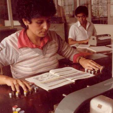 Foto colorida de uma mulher fazendo a transcrição de um livro para o braille.