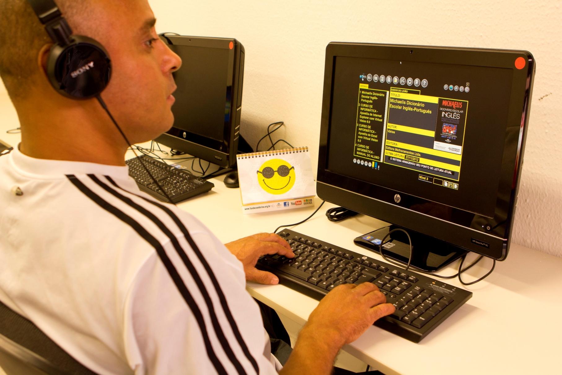 Foto de um homem com deficiência Visual utilizando um Computador, no monitor está aberto um livro digital.