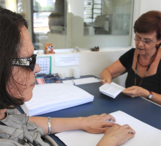 Foto braile de uma senhora lendo um livro em tinta e outra lendo um livro em braile.