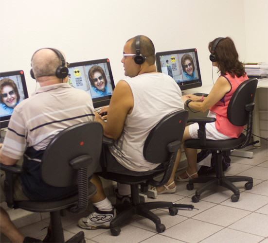 Foto de um curso realizado na Fundação Dorina, há três alunos sentando na frente de computadores.