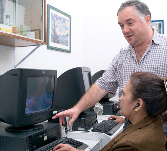 Foto de um instrutor em pé auxiliando uma aluna que está sentada ao computador.