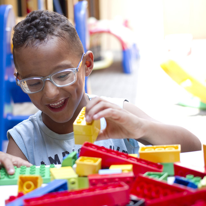 Descrição da imagem: foto de um menino de 6 anos brincando com blocos de montar coloridos. Ele usa óculos e sorri.