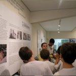 Foto de uma guia da fundação Dorina apresentando o centro de memória para um grupo de meninos