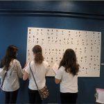 Na foto algumas crianças estão em frente ao quadro branco com letras em braile