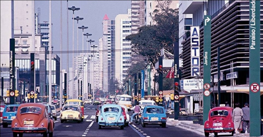 """Imagem destacada: Fotografia antiga da Avenida Paulista na década de 1970. É possível ver vários carros de cores vibrantes entre Fuscas, Brasílias e Variantes. Há placas de sinalização dos bairros Jardins, Paraíso/Liberdade e uma grande placa à direita com o texto """"ASTOR"""", na vertical. Fim da descrição. (Reprodução/Facebook São Paulo Antiga)"""