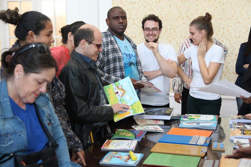 Descrição da imagem: Foto de um grupo de pessoas ao redor de uma mesa de livros.