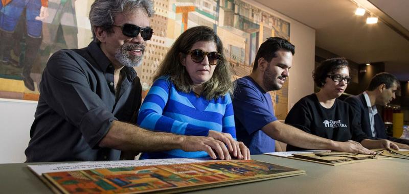 """Descrição da imagem:foto de 5 pessoas tateando a obra adaptada """"Civilização Mineira"""", de Cândido Portinari. Atrás deles está a versão original do quadro """"Civilização Mineira. Fim da descrição."""