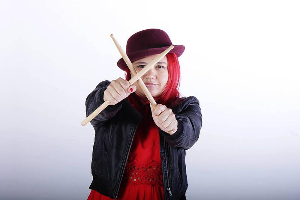 """Descrição da imagem: foto de Bia fazendo um """"X"""" com duas baquetas na frente do rosto. Ela é retratada da cintura pra cima, sobre um fundo branco, com os braços esticados pra frente, usando uma blusa vermelha, jaqueta preta e chapéu vinho. Bia tem a pele clara, cabelos lisos e vermelhos na altura dos ombros, olha pra frente e sorri. Fim da descrição."""