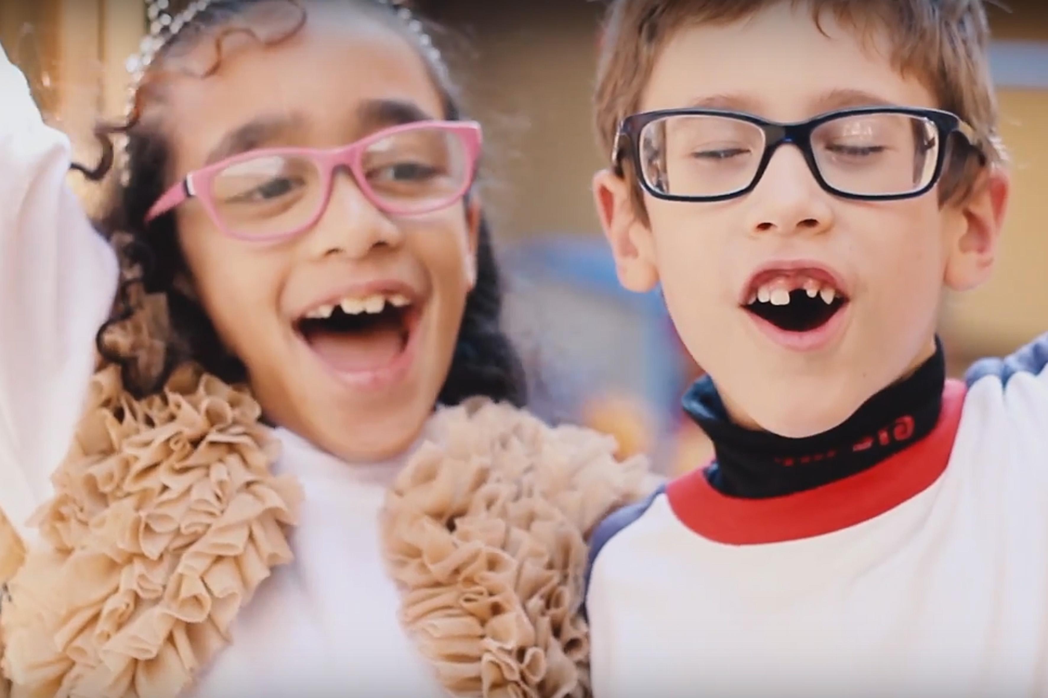 Foto de uma menina e um menino sorrindo.