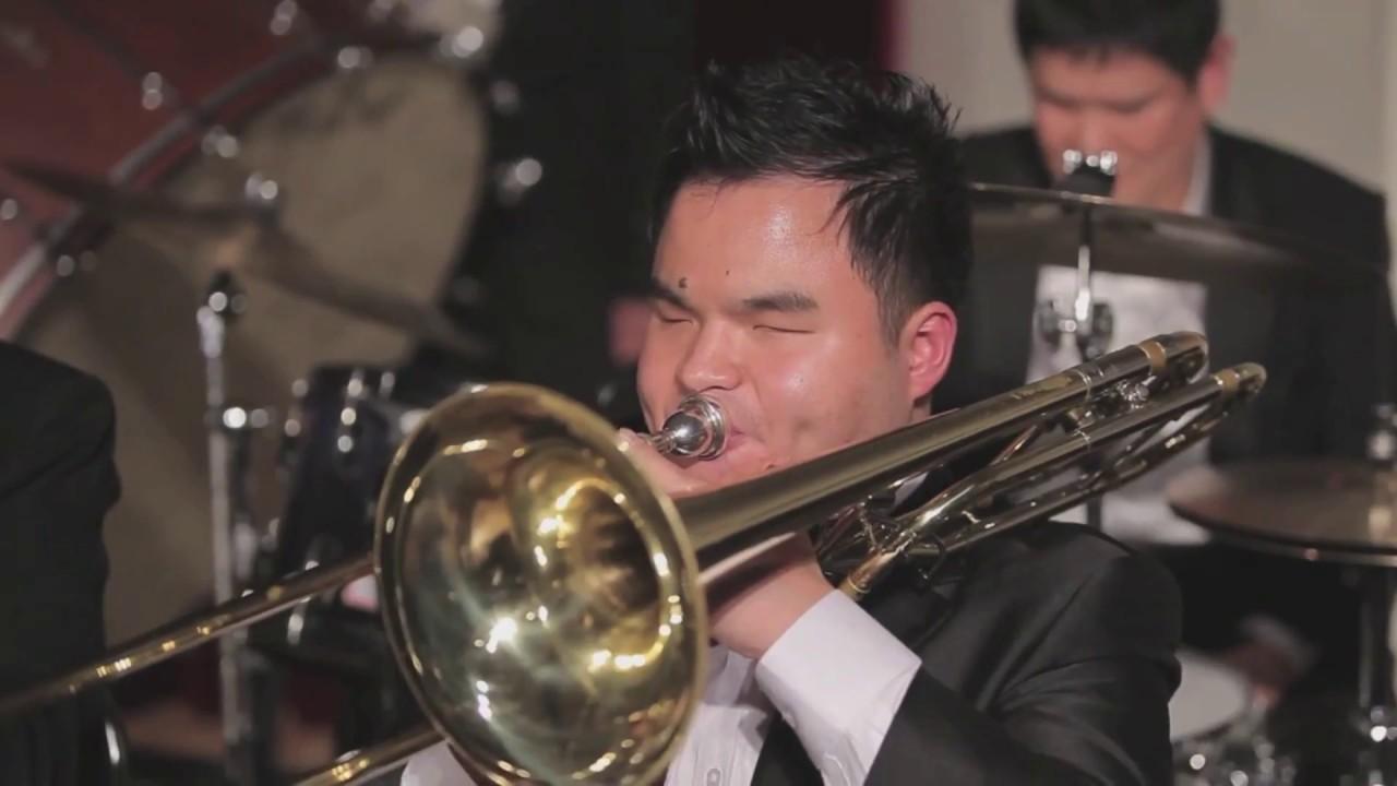 Descrição da imagem: foto de um músico da orquestra retratado do peito pra cima. Ele tem cabelos curtos, traços orientais, veste terno preto com camisa branca e sopra um trombone com os olhos fechados. Fim da descrição.