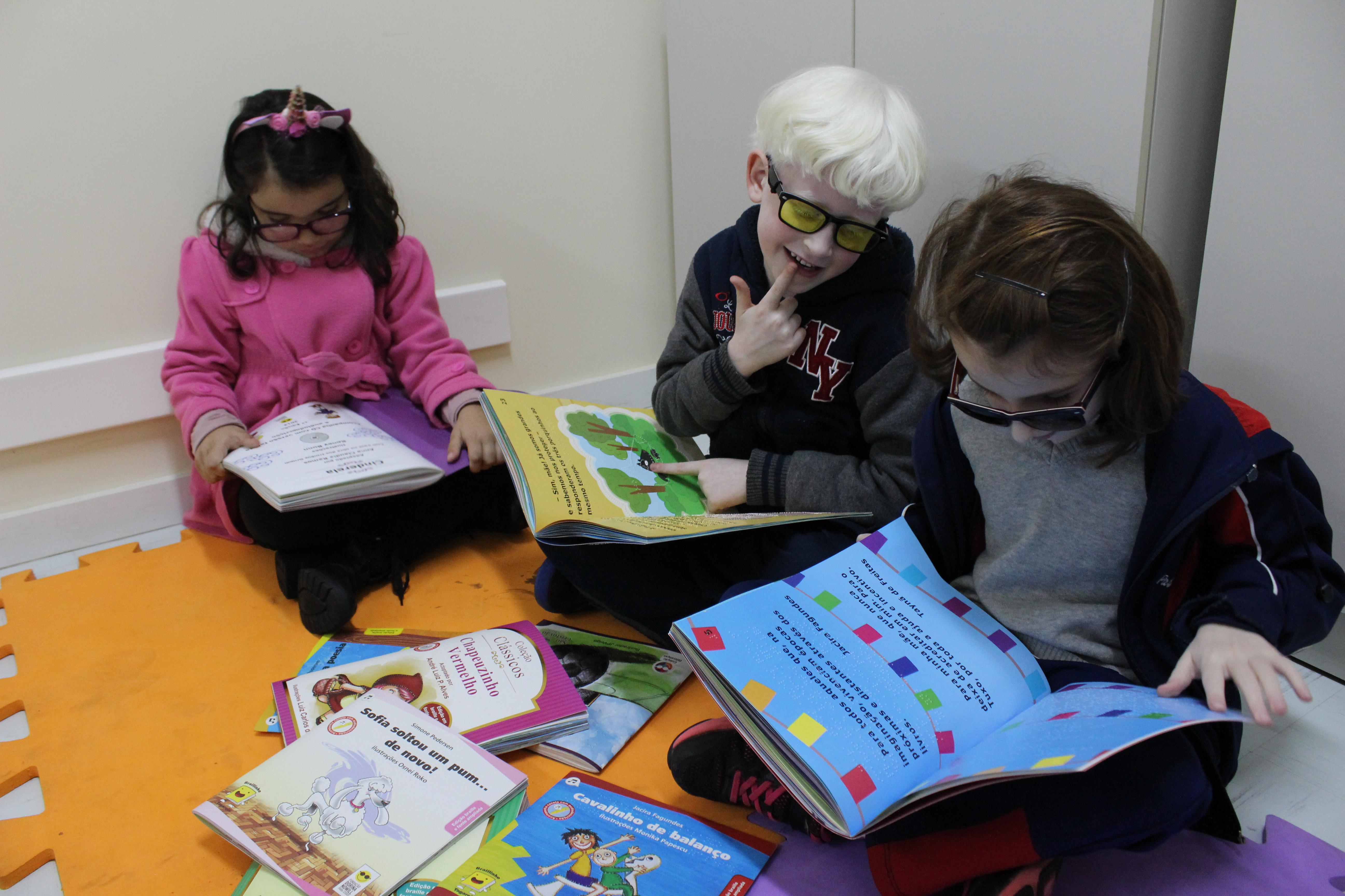 Descrição da imagem: Três crianças, duas garotas e um garoto, sentados sob tapetes coloridos, leem livros em braile. Fim da descrição de imagem.