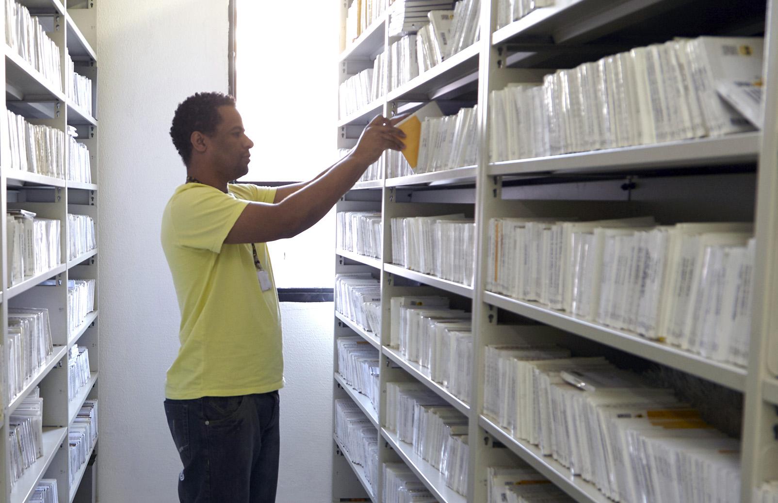 Foto de um dos funcionários da biblioteca da Fundação Dorina retirando um livro de uma prateleira.