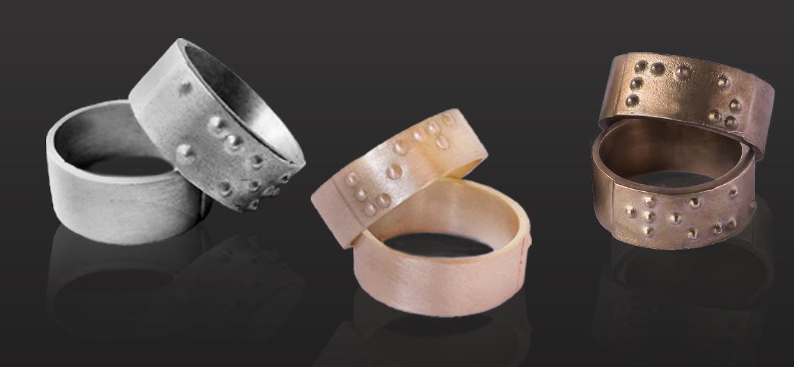 Descrição da imagem: foto de 6 anéis em prata, ouro e bronze com pontos em braile. Fim da descrição.