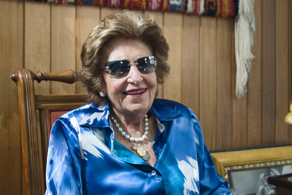 Descrição da imagem: foto de Dorina Nowill. Ela usa camisa azul, óculos escuros, olha pra frente e sorri. Fim da descrição.