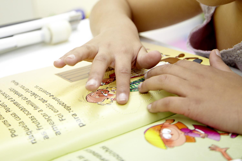 Descrição da imagem: foto de duas mãos tateando um livro em tinta e braile infantil. A página do livro é amarela e tem desenhos de um senhor e uma garotinha. Fim da descrição.