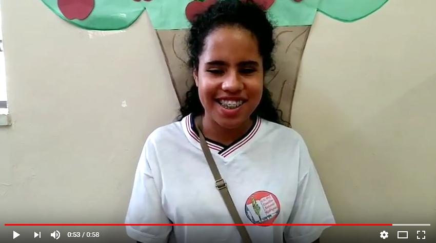 Descrição da imagem: imagem capturada do vídeo vencedor. Nela aparece a aluna Suellen sorrindo, na frente de uma parede com o desenho de uma árvore. Ela é morena, tem cabelos pretos e compridos, usa aparelho e uniforme escolar na cor branca. Fim da descrição.