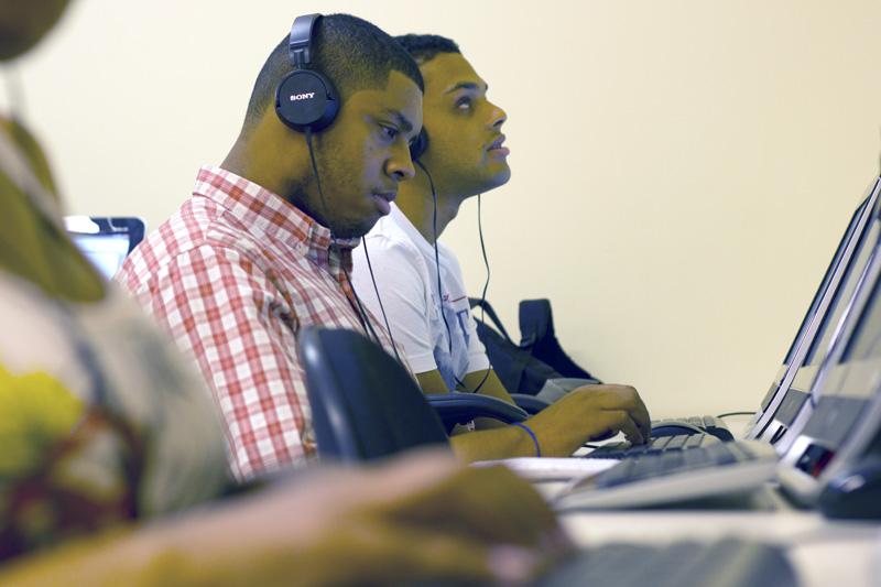 Descrição da imagem: foto de dois rapazes de perfil, em frente a computadores. Eles usam fones de ouvido pretos.