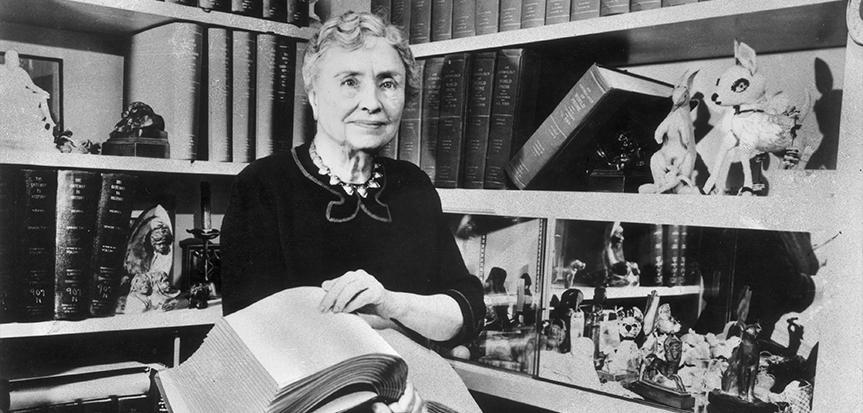 Descrição da imagem: foto em preto e branco de Helen Keller segurando um grande livro em braille. Atrás dela há uma estante repleta de livros e objetos decorativos. Ela tem cabelos grisalhos, usa blusa preta, olha pra frente e exibe um sorriso discreto.
