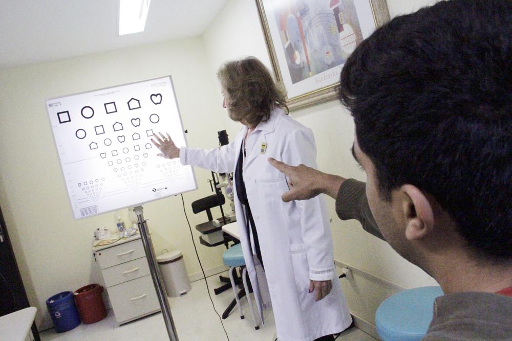 Descrição da imagem: Foto de um homem e uma médica. Ele está fazendo uma avaliação oftalmológica.
