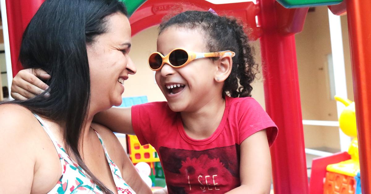 Descrição da imagem: foto de Julia com o braço sobre os ombros da mãe Alessandra no parquinho da Fundação Dorina. Elas se olham e sorriem.
