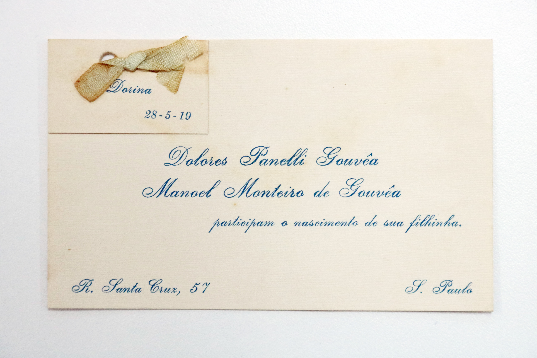 """Foto de envelope com o nome dos pais de Dorina e o texto """"participam o nascimento de sua filhinha""""."""