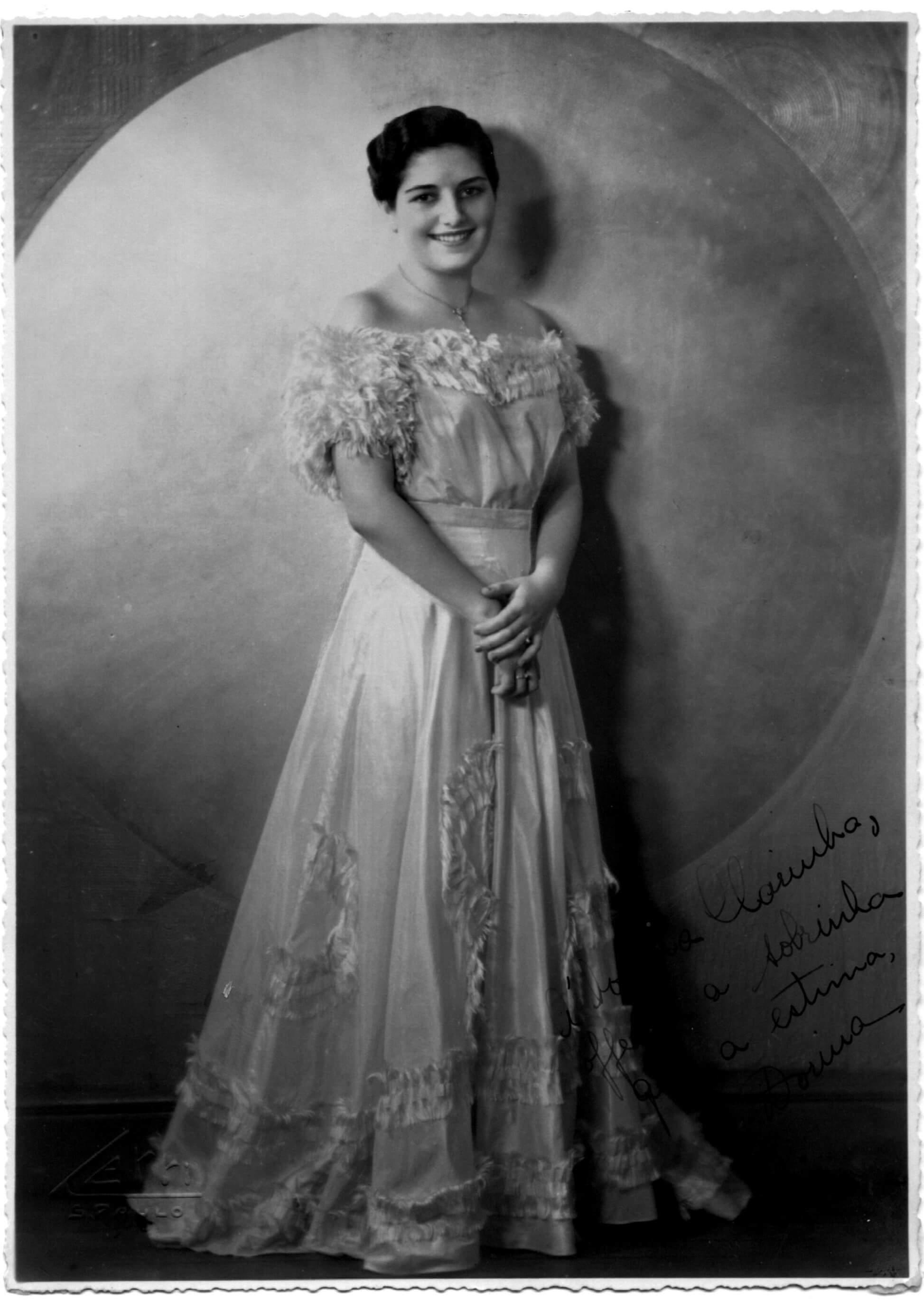 Foto em preto e branco de Dorina sorrindo, de vestido branco.