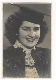 Foto de Dorina sorrindo. Ela usa uma beca, traje típico de formatura, e chapéu.