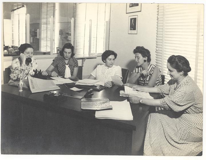 Foto em preto e branco de Dorina e outras mulheres sentada numa mesa com outras mulheres