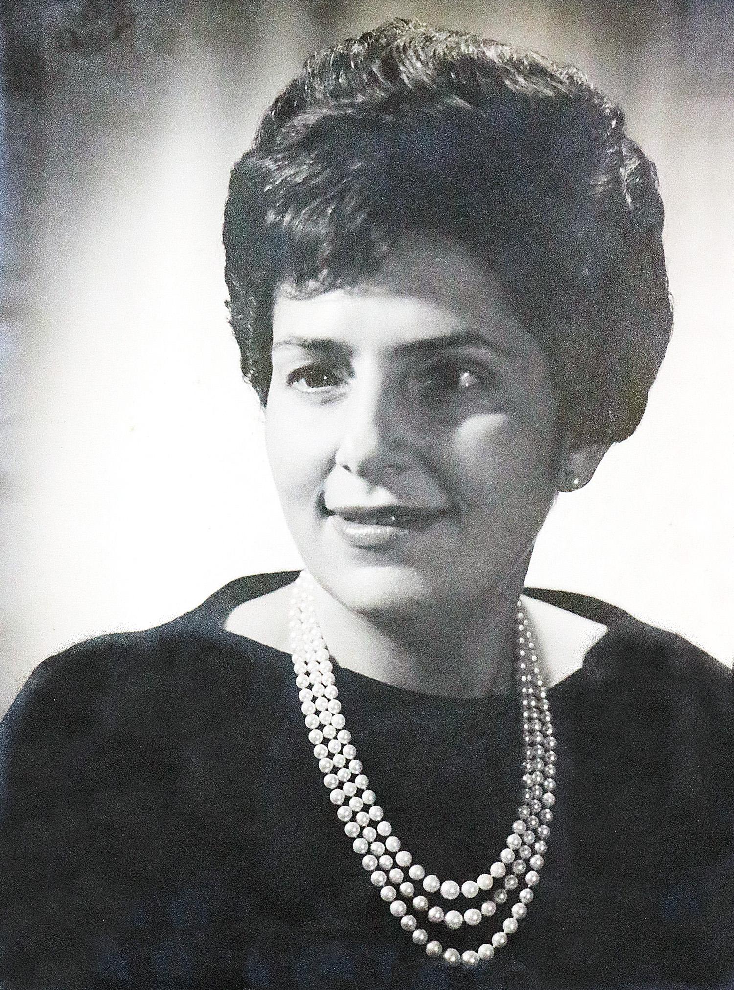 Foto em close em preto e branco de Dorina sorrindo, olhando para o lado. Ela usa roupa preta e colar de pérolas.