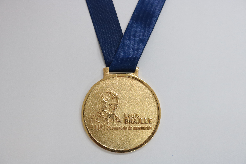 Foto da medalha comemorativa dos 200 anos de Braille